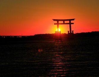 湖に立つ鳥居と夕日