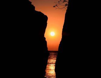神割崎の間から上る太陽